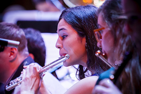 Woman plays a flute with the Jazz band