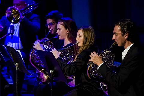 Brass section of the Jazz band dressed in black plays during a performance on stage