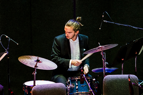 Drummer looks to his right while behind the drums during a performance