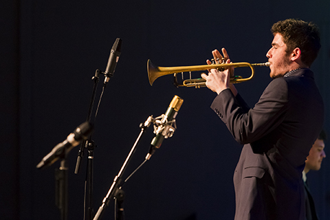 Trumpet player in a black suit performs a solo during an event