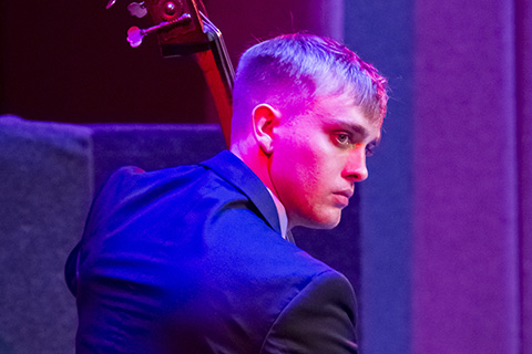 Upright bass player performing live on stage