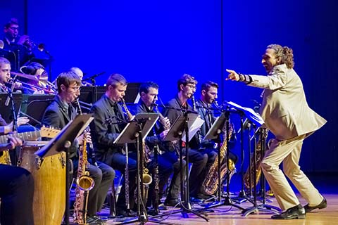 Conductor motions to his left while a group of Jazz players perform on stage