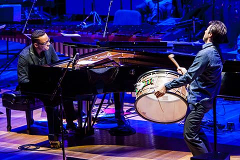 Man in the blue dress shirt plays a single drum while a man in a dark shirt  plays a piano
